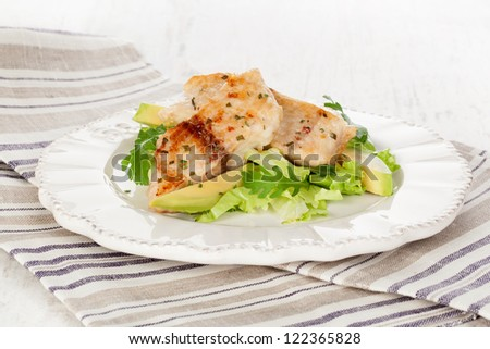 Healthy eating. Grilled fish fillet with fresh rocket salad, lettuce and avocado on white plate on white wooden textured background. - stock photo