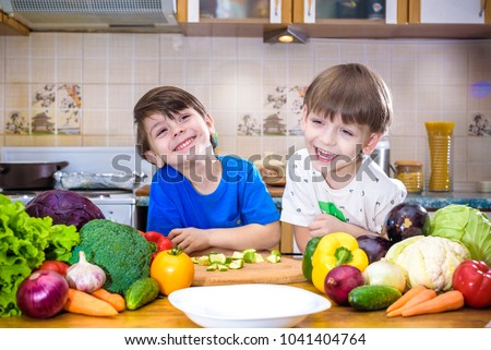 Healthy eating. Happy children prepares and eats vegetable salad in kitchen. Health and friendship concept.