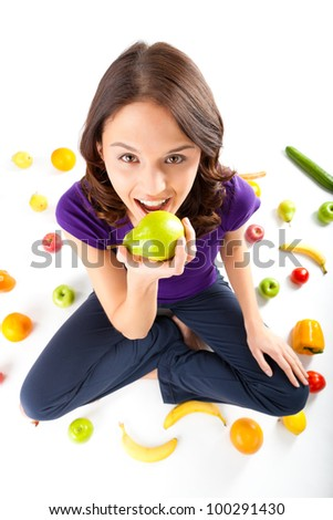 Healthy eating, happy woman with fruits and vegetables is eating a pear
