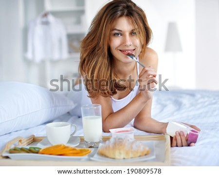 Healthy eating / happy young woman having breakfast in bed  - stock photo