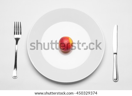 Healthy eating in the restaurant and diet Topic: beautiful ripe nectarine on a white plate with a metal knife and fork lies on an isolated white table in studio top view - stock photo
