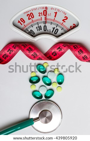 Healthy eating, medicine, health care, food supplements and weight loss concept. Pills with measuring tape and stethoscope on white scales - stock photo