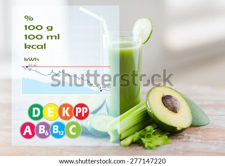 healthy eating, organic food and diet concept - close up of fresh green vegetable juice glass and vegetables on table with calories and vitamin chart - stock photo