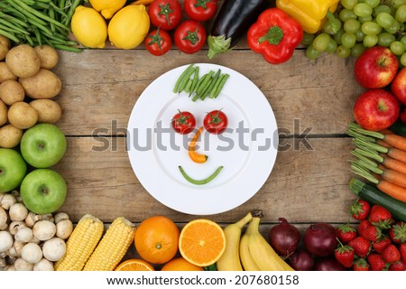 Healthy eating smiling face from vegetables and fruits on plate - stock photo