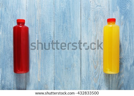 Healthy eating. Smoothie vegan drinks flat lay, top view at blue rustic wood background. Berry and orange healthy, dieting energetic fruit drinks in bottles with copyspace. Smoothie in bottles. - stock photo