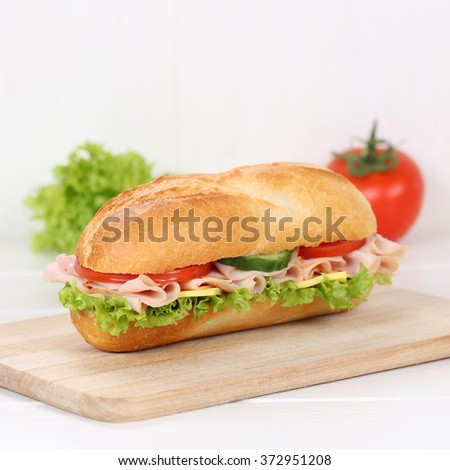 Healthy eating sub deli sandwich baguette with ham, cheese, tomatoes and lettuce for breakfast - stock photo