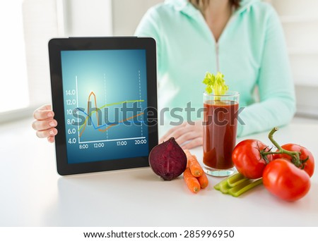 healthy eating, technology, diet and people concept - close up of woman hands holding tablet pc computer with chart, tomato juice and vegetables at home - stock photo