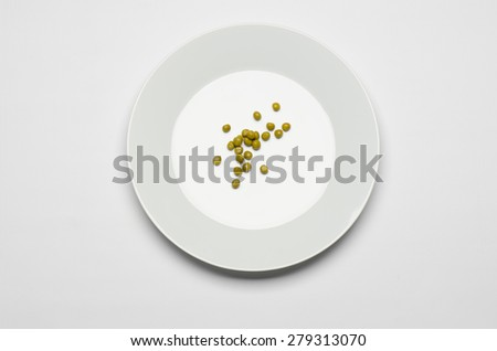Healthy eating topic: green peas lying on a white plate on a white table in the studio top view - stock photo