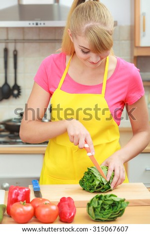 Healthy eating, vegetarian food, cooking, dieting and people concept. Woman in modern kitchen at home preparing fresh vegetables salad closeup