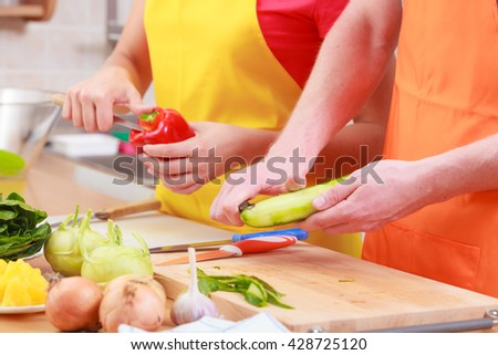 Healthy eating, vegetarian food, cooking, weight loss and people concept. young couple woman and man in kitchen at home preparing fresh vegetables salad meal, close up