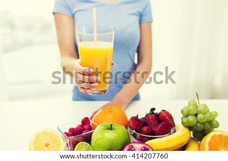 healthy eating, vegetarian food, diet and people concept - close up of woman holding orange juice glass with fruits at home