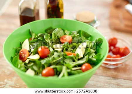 healthy eating, vegetarian food, dinner, cooking and culinary concept - close up of salad bowl and spices on kitchen table - stock photo
