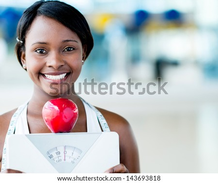 Healthy eating woman holding scale and an apple - stock photo