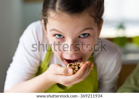Healthy eating, young girl eating walnuts - stock photo