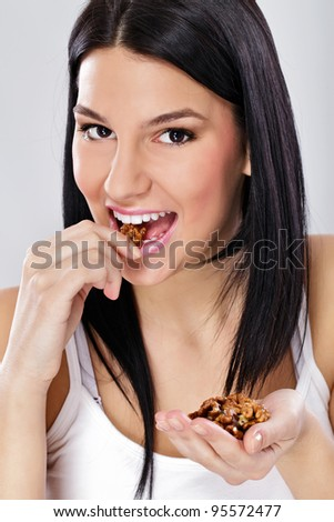 Healthy eating, young woman eating shelled nuts