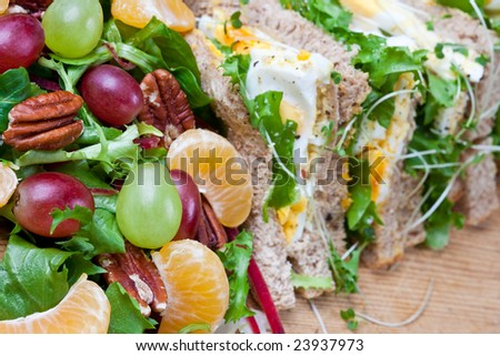 Healthy egg sandwich with salad and walnuts (focus on fruit)