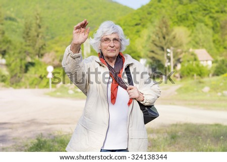 healthy elderly woman looking up with arms outstretched outdoors - stock photo