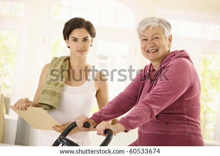 Healthy elderly woman training at home with exercise bike, assisted by personal trainer.?