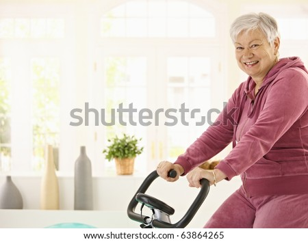 Healthy elderly woman training at home with exercise bike, smiling.? - stock photo