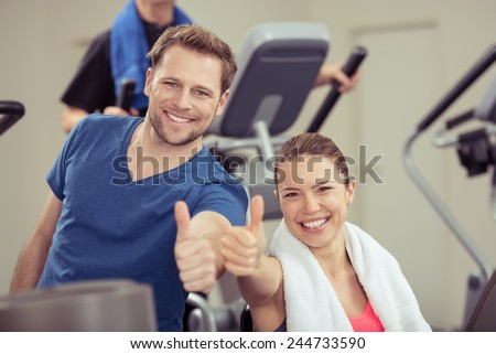 Healthy enthusiastic young couple in a gym giving a thumbs up of approval while smiling at the camera in a health and fitness concept - stock photo