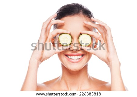 Healthy eyes. Beautiful young shirtless woman holding slices of cucumber in front of her eyes while standing against white background - stock photo