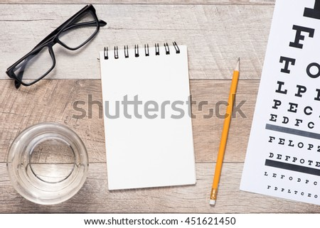 Healthy eyes. Eye chart and notebook with copy space - stock photo