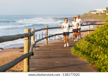 healthy family running by the beach - stock photo