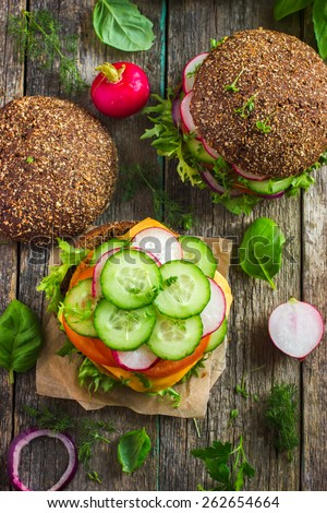 Healthy fast food. Rye burgers with fresh vegetables, chickpeas patty and cheese on old wooden  background, top view - stock photo