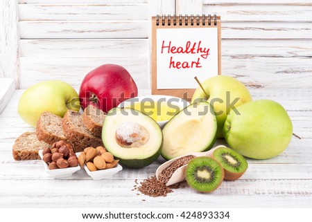 Healthy fat sources and healthy food that is useful for the heart on wooden background with note Healthy heart. Diet and healthy lifestyle concept. Copy space - stock photo