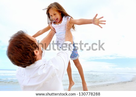 Healthy father and daughter playing together at the beach carefree happy fun smiling lifestyle - stock photo
