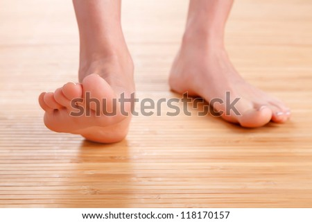 Healthy female feet on wooden floor