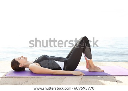 Healthy female on yoga mat relaxing her mind and body with blue sea in background, nature outdoors. Woman doing sport training and exercising, body and mind control activities, recreation lifestyle.