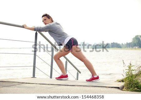 Healthy female runner stretching during running or jogging workout outdoor. Wearing fitness clothing. - stock photo