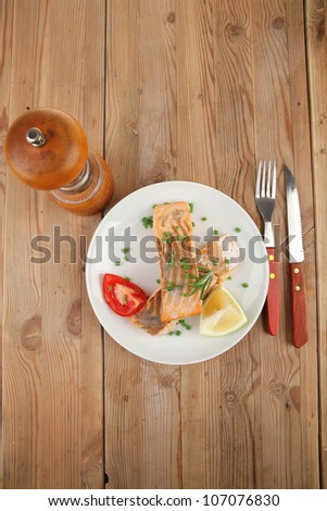 healthy fish cuisine : baked pink salmon steaks with green onion, cherry tomatoes, small pepper grinder, rosemary twigs and lemon on wooden board