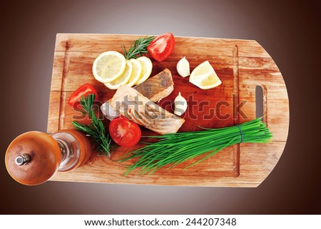 healthy fish cuisine : baked pink salmon steaks with green onion, cherry tomatoes, small pepper grinder, rosemary twigs and lemon on wooden board isolated on white background - stock photo