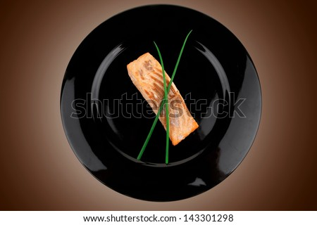 healthy fish cuisine : baked pink salmon steaks with green onion on black dish isolated over white background - stock photo