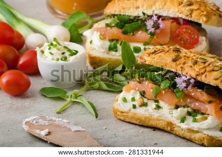 Healthy Fish snack - wholemeal baguette with cream cheese, seeds and smoked salmon with fresh herbs - stock photo