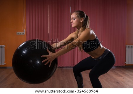 Healthy Fit Woman Holding Black Fitness Ball While Doing Stretching Exercise Inside the Gym. - stock photo