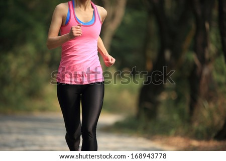 healthy fit woman runner running in forest trail