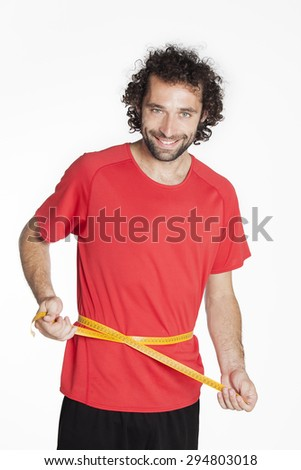 Healthy fit young man measuring his waist with a measure tape. Smiling at the camera, isolated on white
