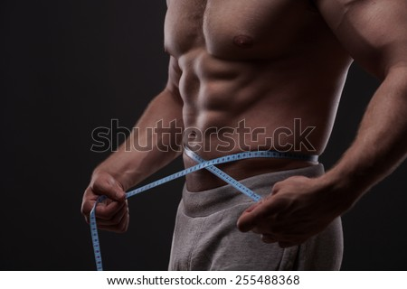 Healthy fit young man measuring his waist with a tape measure isolated on dark background - stock photo