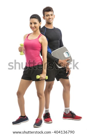 Healthy fitness people with a weight scale and dumbbell on white background. - stock photo