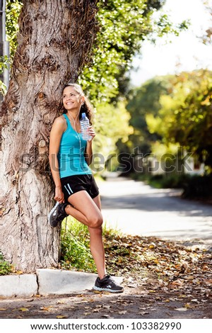 healthy fitness woman resting with water bottle after workout exercise session. vitality lifestyle runner.