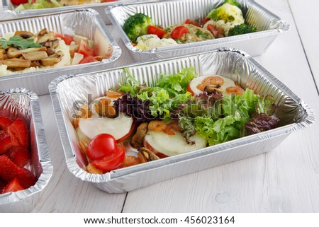 Healthy food and diet concept. Take away of fitness meal. Weight loss nutrition in foil boxes. Vegetables, lettuce and mozarella cheese with cherry tomatoes and shrimps closeup at white wood - stock photo