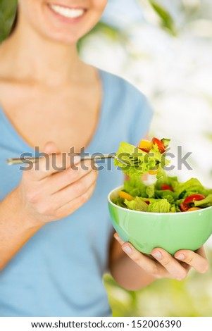 healthy food and dieting concept - woman eating salad with vegetables