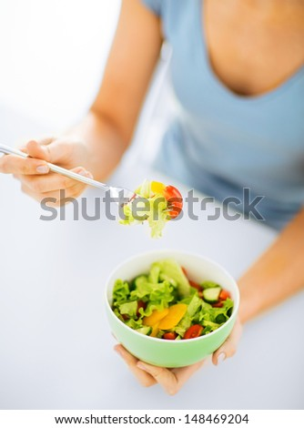 healthy food and kitchen concept - woman eating salad with vegetables - stock photo