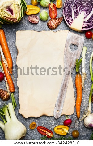Healthy food and tasty vegetarian cooking background with assortment of colorful farm vegetables around blank sheet of paper with wooden spoon , top view, frame.  - stock photo