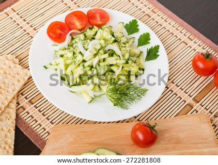 Healthy food. Appetizer. Fresh cucumber salad with onion, dill and cherry tomatoes - stock photo