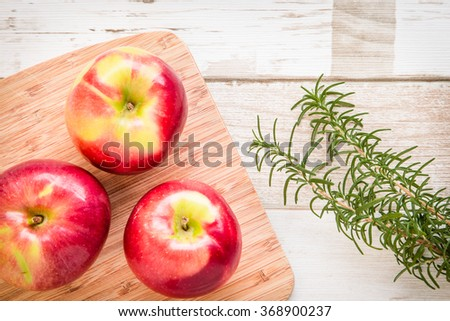 Healthy food arrangement with three red apples on a wooden board and rosemary leaves on a rustic wooden table. View from above/top.