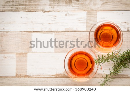 Healthy food arrangement with two glass cups of herbal or black tea and rosemary leaves on a rustic wooden table. View from above/top. Copy space.